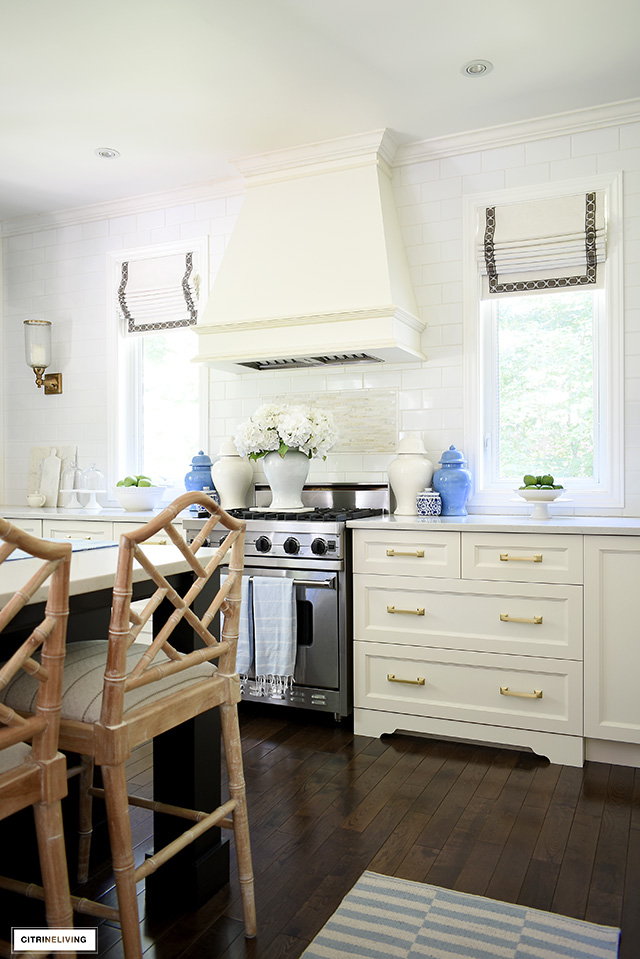 White kitchen with beautiful ginger jars, blue and white striped rug and faux hydrangeas.