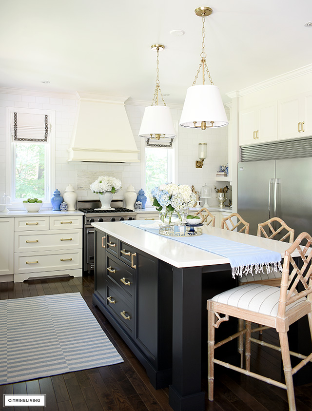 Gorgeous white kitchen with black island, blue and white ginger jars, striped rugs and hydrangeas.