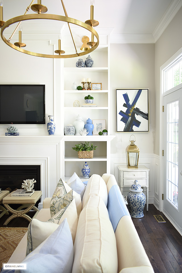 Living room shelves with beautiful objects - ginger jars, blue and white ceramics, coral, baskets, greenery and gold frames.