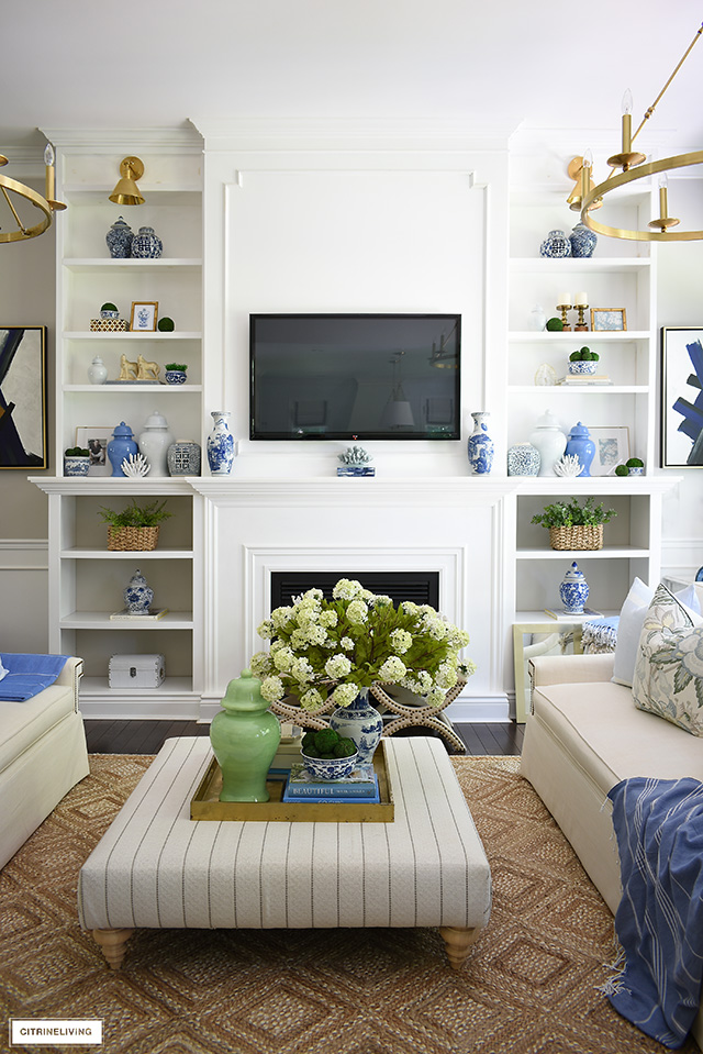 Builtin bookshelves with ginger jars, baskets, greenery, coral gold frame create an elegant curated look in this summer decorated living room.