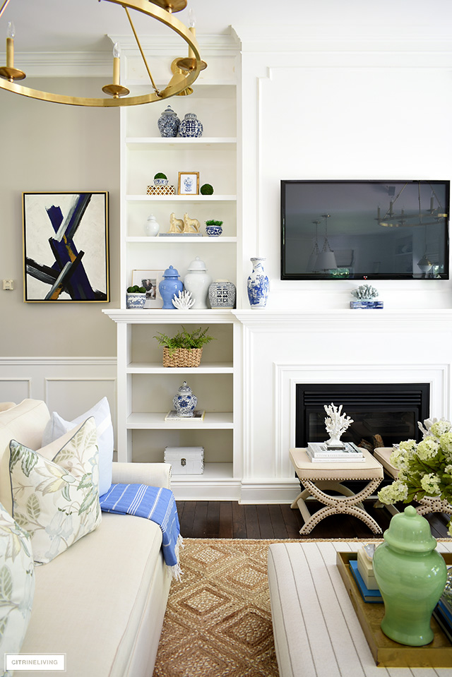 Bookshelves summer decorated with beautiful ginger jars, coral, baskets and greenery.