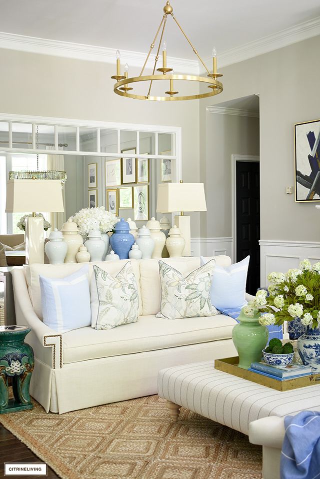 Living room decor, white sofa decorated with beautiful floral pillows, light blue pillows. Gorgeous jute rug and blue and green accents are perfect for summer!