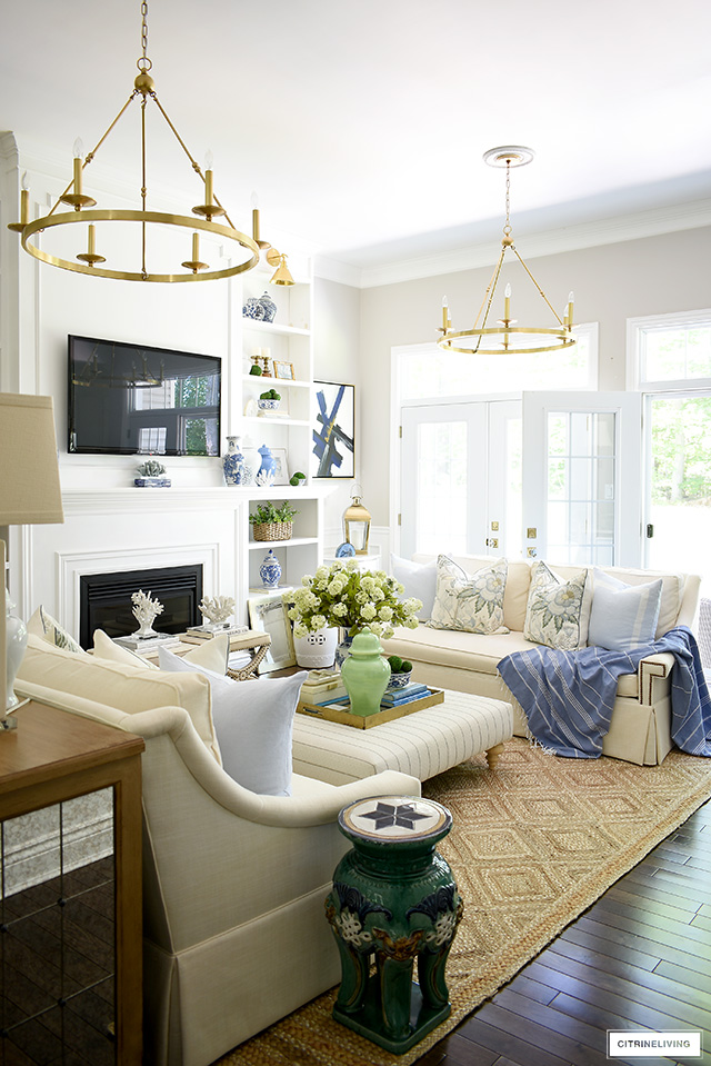 Summer decorated living room - blue, white and green accents, jute rug and floral pillows. A fresh and breezy palette perfect for hot summer days!