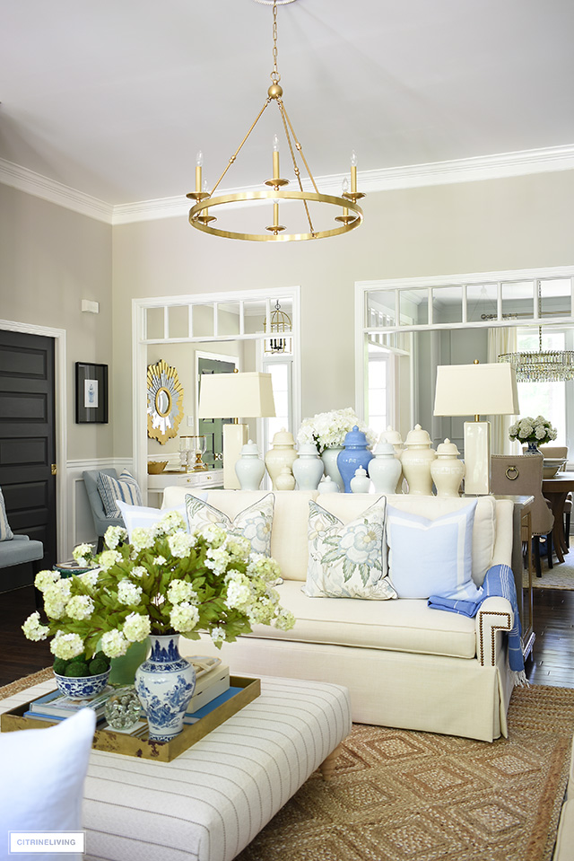 Living room decorated for summer with beautiful blue and green floral pillows, blue pillows, ginger jars and a natural jute rock.