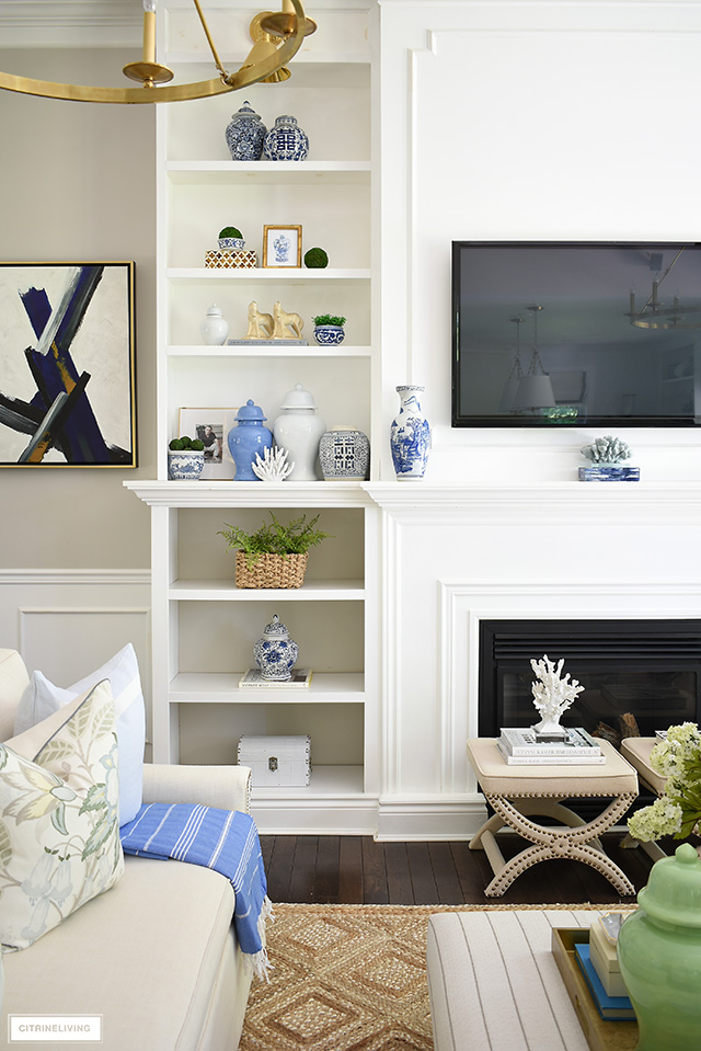 Bookshelves decorated for summer with beautiful blue ginger jars, blue and white chinoiserie, greenery and natural elements.