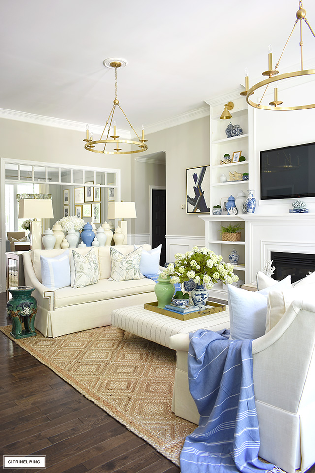 A gorgeous summer decorated living room theme with a natural jute rug, green and blue ginger jars, floral pillows, light blue pillows and greenery accents.