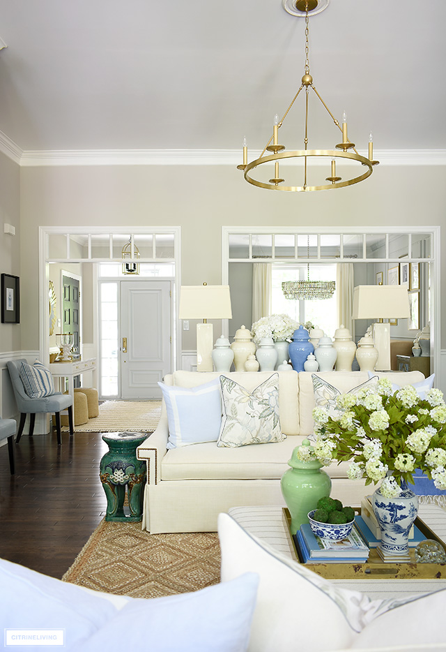 Living room decorated for summer with a fresh, blue, green and white color palette with a natural jute rug.