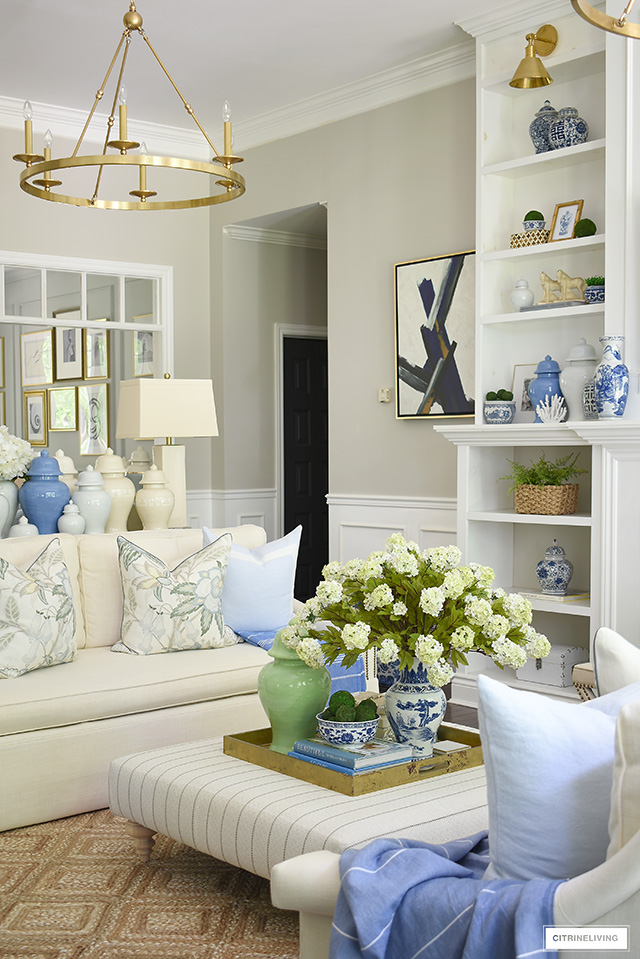 Living room ottoman decorated for summer with a large tray, faux hydrangeas a green ginger jar and blue and white chinoiserie.