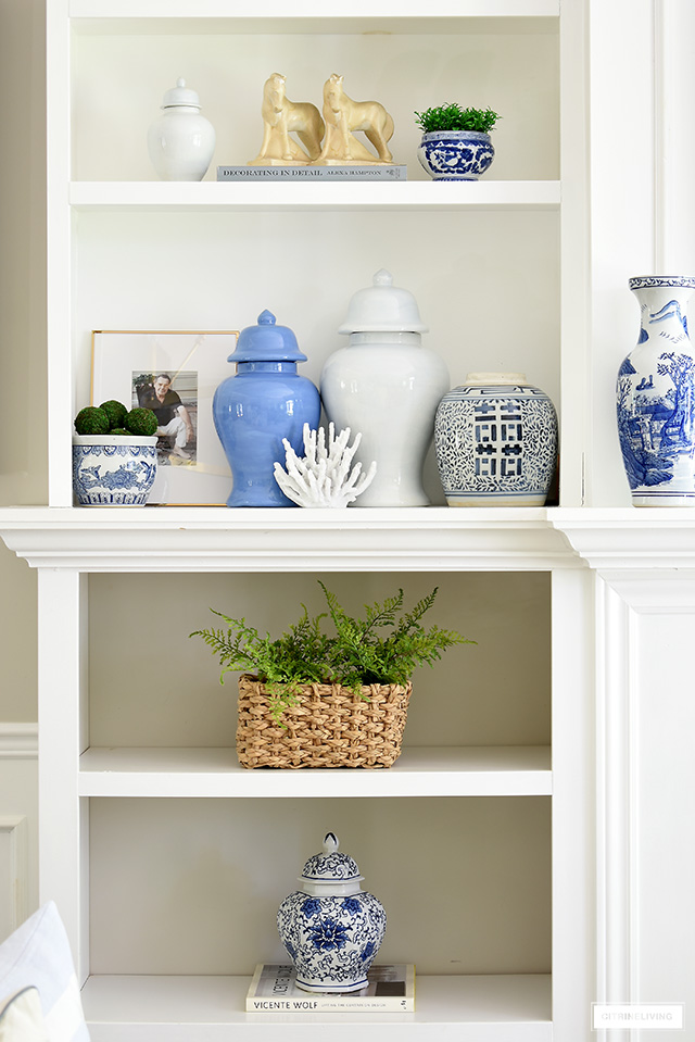 Gorgeous styled bookshelves with blue ginger jars, blue and white bowls and vases, greenery and beautiful collected objects.