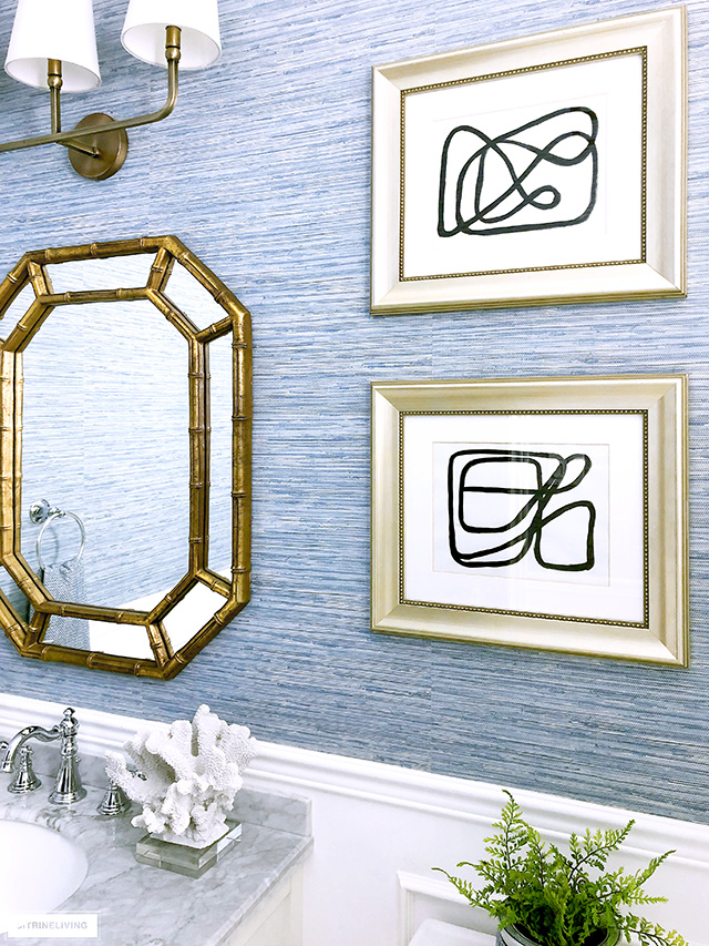 Coastal-chic bathroom with abstract linear art in gold frames.