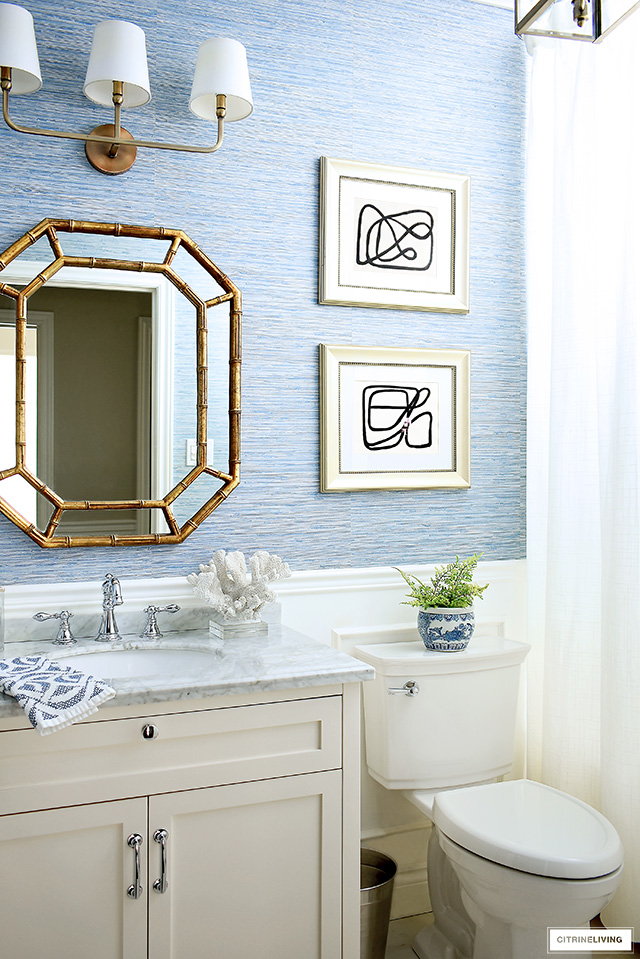 Blue and white coastal-chic bathroom with gold accents, abstract art, a white vanity and blue grasscloth wallpaper.