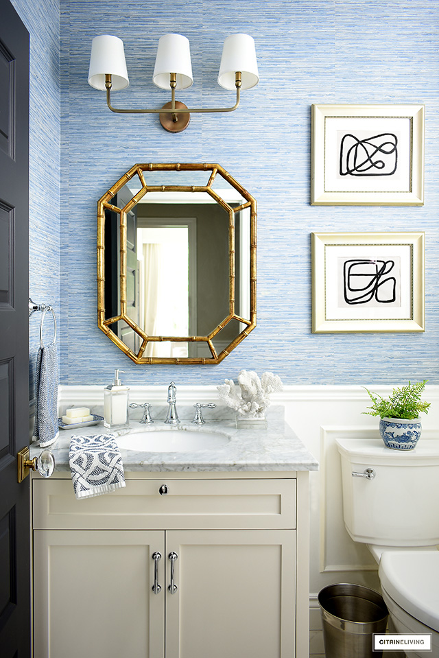 Blue and white coastal-chic bathroom with white vanity, silver hardware and faucet, gold mirror and lighting and blue grasscloth wallpaper.