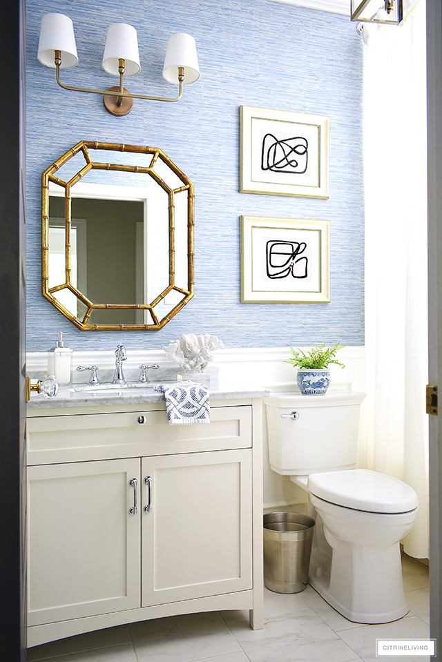 Coastal-Chic bathroom decor with a white vanity, regency style mirror, brass lighting and blue grasscloth wallpaper.