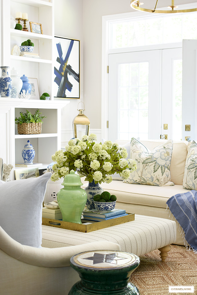 Gorgeous living room details for summer - ottoman decorated with a large gold tray, green ginger jar, blue and white bowl with moss balls, a large-scale faux snowball hydrangea arrangement.