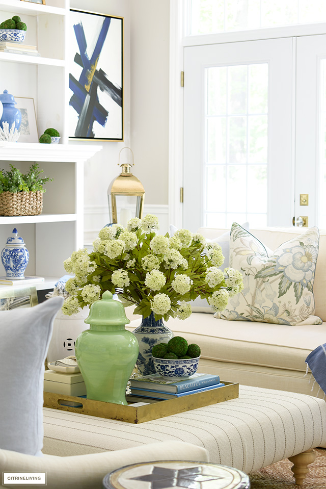 A gorgeous summer vignette with a large-scale floral arrangement, green ginger jar, blue and white chinoiserie.