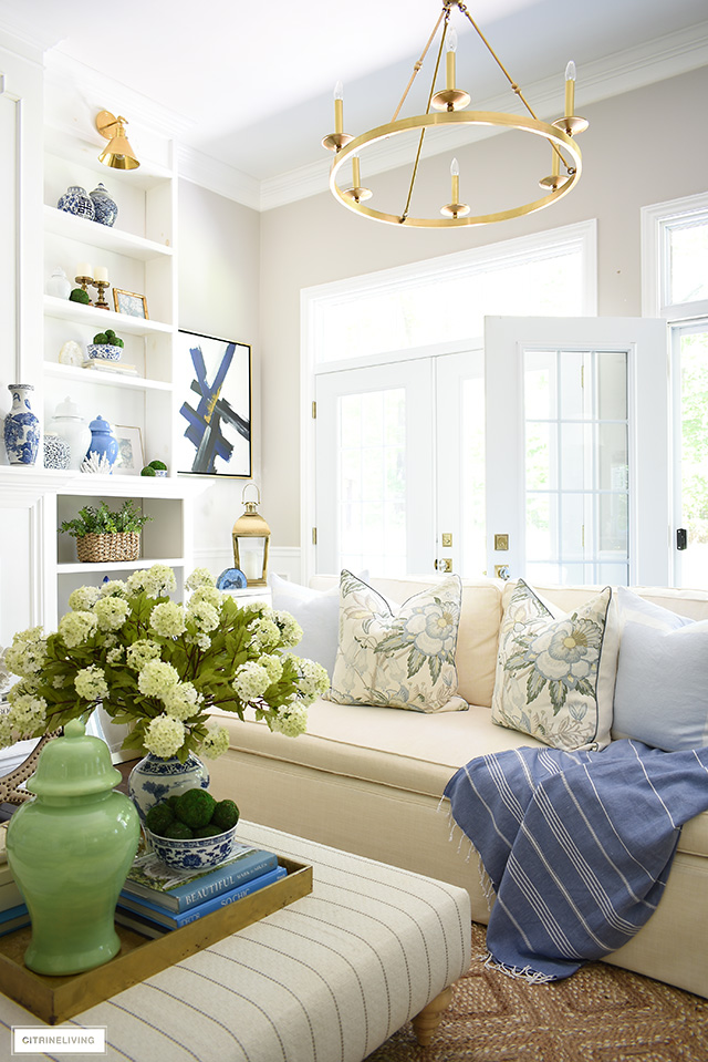 Summer decorated living room with gorgeous floral pillows and a blue and green color platte.