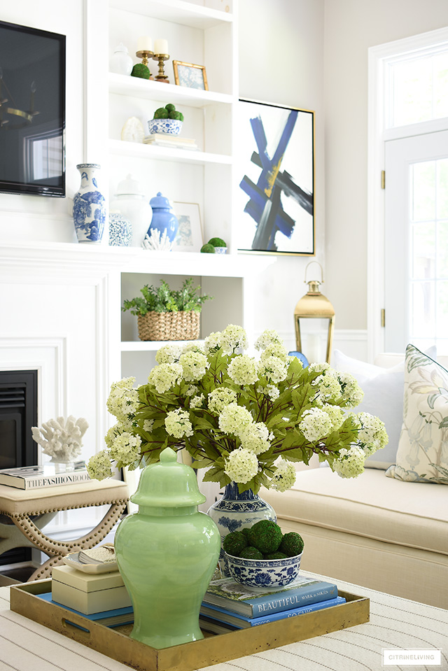A gorgeous summer vignette with a large-scale floral arrangement, green ginger jar, blue and white chinoiserie and design books.