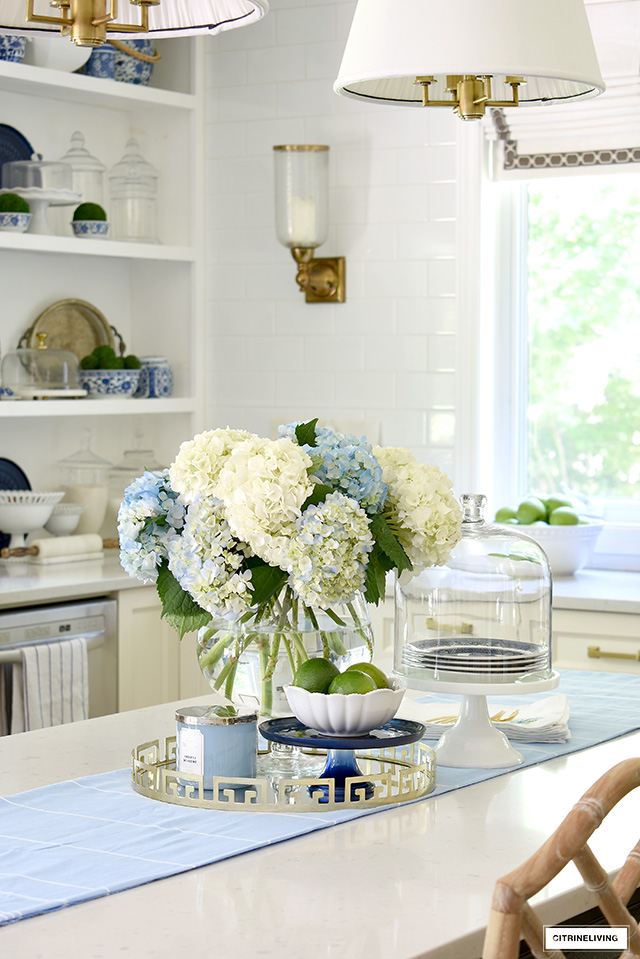 Fresh cut blue and white hydrangeas styled on a gold tray with a bowl of limes - the perfect summer centrepiece!