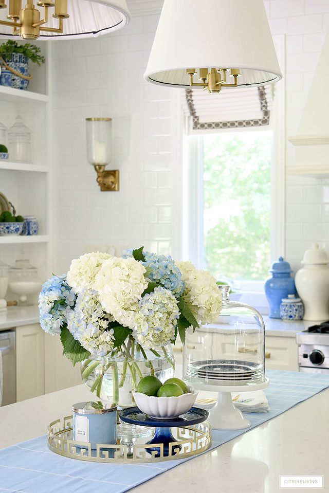 Beautiful blue and white hydrangeas for summer styled on a gold tray with a bowl of fresh limes.