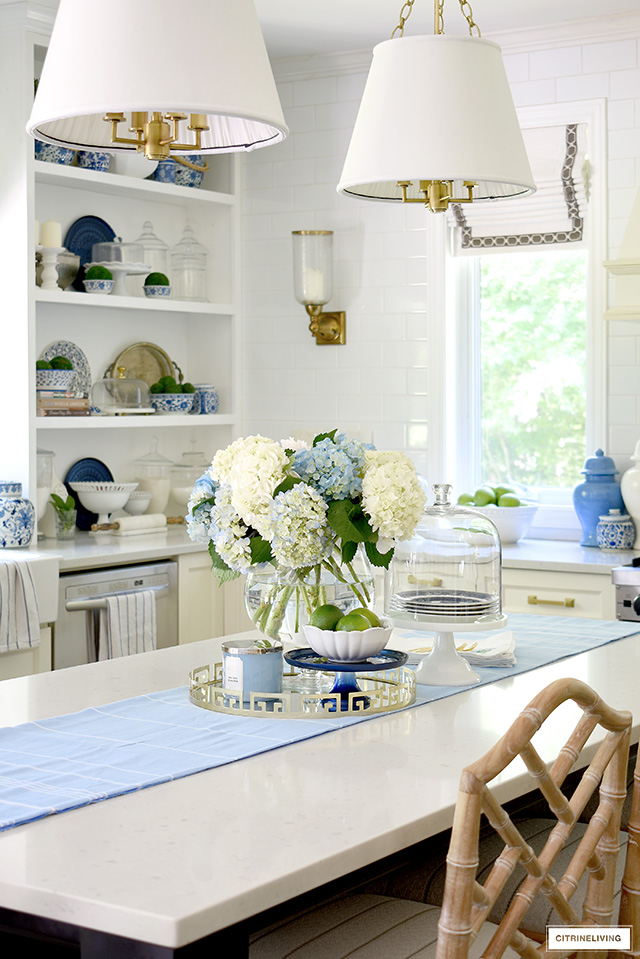 Beautiful kitchen styled with blue and white hydrangeas, fresh limes, green apples and blue and white accents.