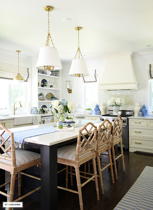 Summer decorated kitchen with blue and white accents, striped rugs, greenery and hydrangeas.