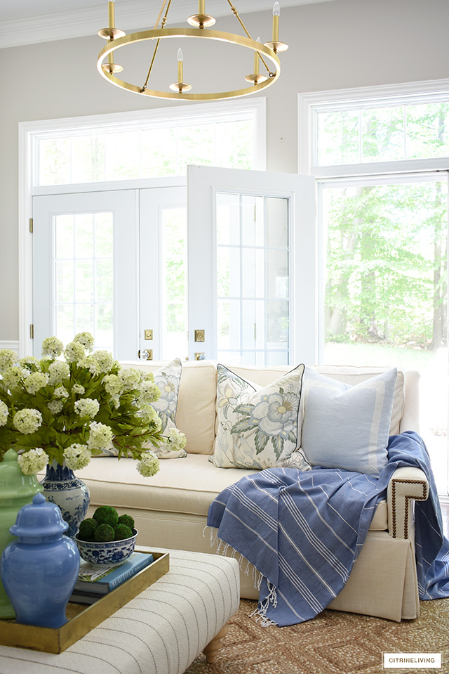 Summer decorated living room - white sofa, beautiful floral pillows, blue and green ginger jars and a natural jute rug are breezy and refreshing for summer.