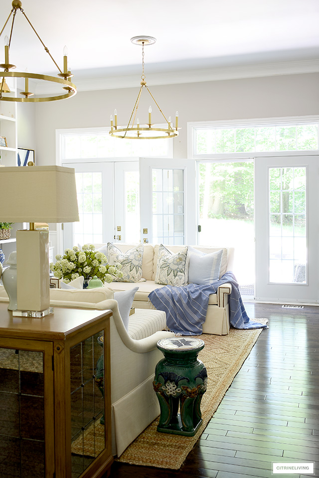 Summer living room with a beautiful jute rug, white sofas, blue and green accents that are casual and elegant.