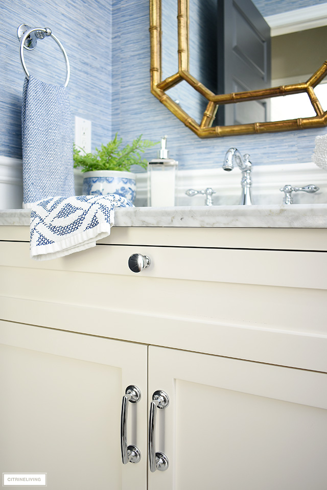 Elegant coastal-chic bathroom with classic details - white vanity, silver hardware and accessories.