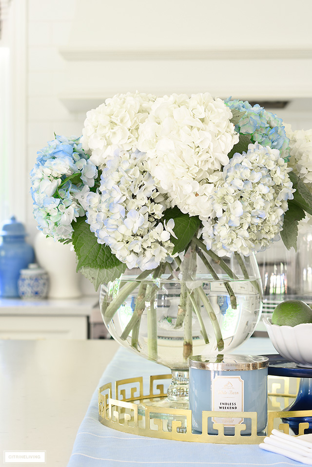 Blue and white hydrangeas arranged in a large glass bowl.
