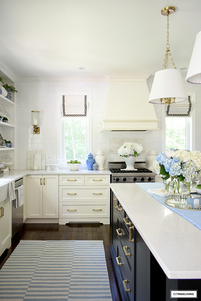 Summer decorated kitchen with a coastal vibe - blue and white striped rug, ginger jars and hydrangeas.