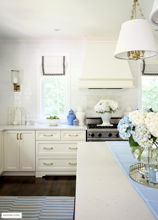 Summer kitchen decorating - blue and white striped rugs, ginger jars and hydrangeas for a crisp and airy feel.