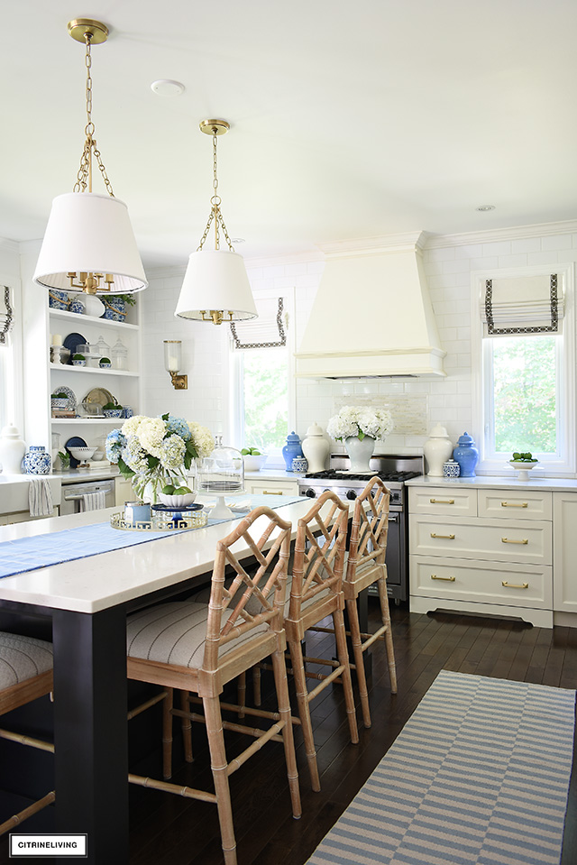 Beautiful kitchen with striped rugs, ginger jars, blue and white accents and greenery.