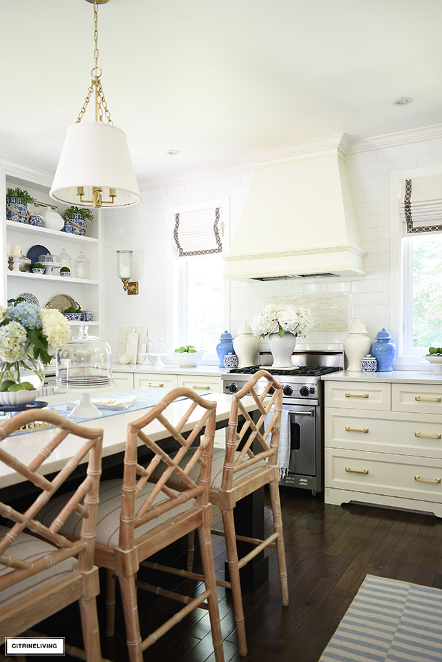 Summer kitchen decorated with blue and white ginger jars, flowers and striped rugs.