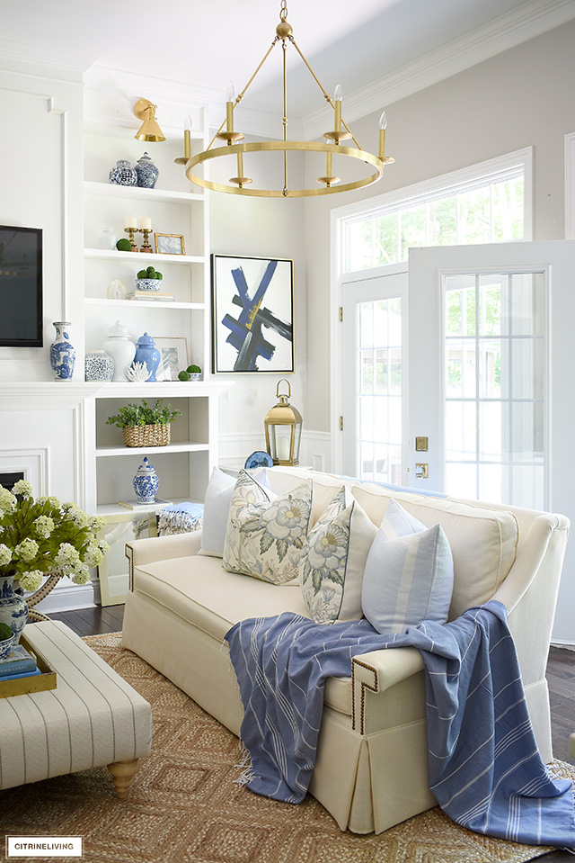Beautiful summer living room decorating with blue and green accents, a natural jute rug, floral and blue designer pillows.