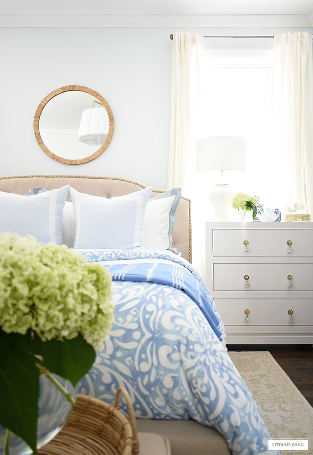 Summer bedroom decorated with a round rattan mirror, blue bedding and fresh hydrangeas
