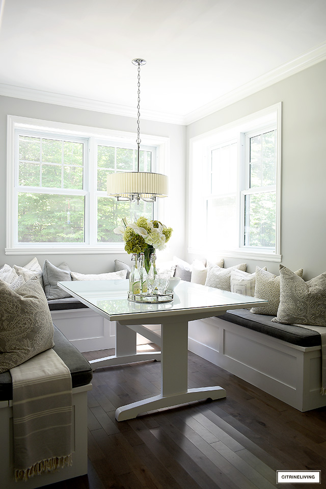 Gorgeous kitchen breakfast nook, filled with lush pillows in grey and cream prints.