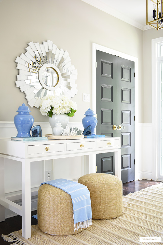 Entryway console table with ginger jars, coral and agate. Accented with woven poufs and white sunburst mirror.