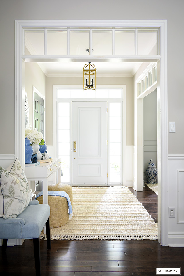 Entryway decorated for summer with a pretty blue, white and natural palette.