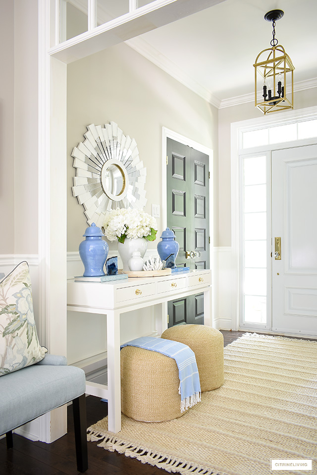 Summer entryway with white console table, blue ginger jars, white sunburst mirror and woven poufs and rug.