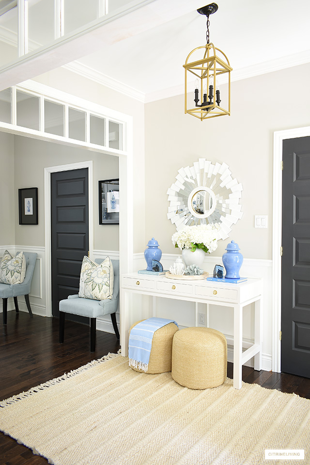 Summer entryway with white and blue decor, natural jute rug and poufs, and white sunburst mirror.