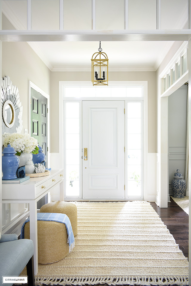 Entryway decorated for summer with white and blue decor, woven jute rug and poufs.