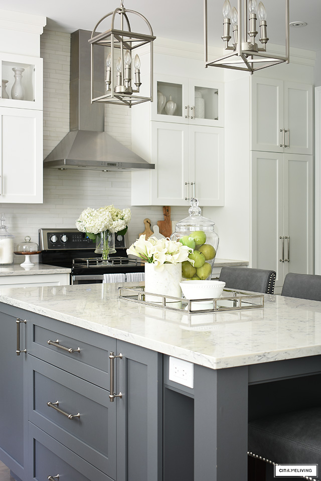 White kitchen with grey island, brushed silver hardware and lighting.