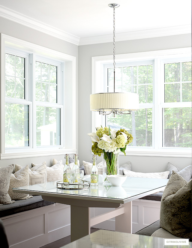Beautiful breakfast nook with drum shade pendant light, built-in benches and layers of grey and cream printed pillows.