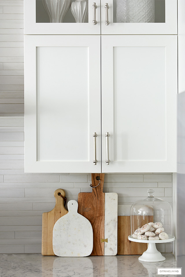 Beautiful shaker style white cabinets with satin nickel handles, wood and marble cutting boards leaning against tile backsplash.