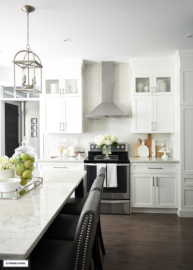White kitchen with silver hardware, hardwood floors and grey island.