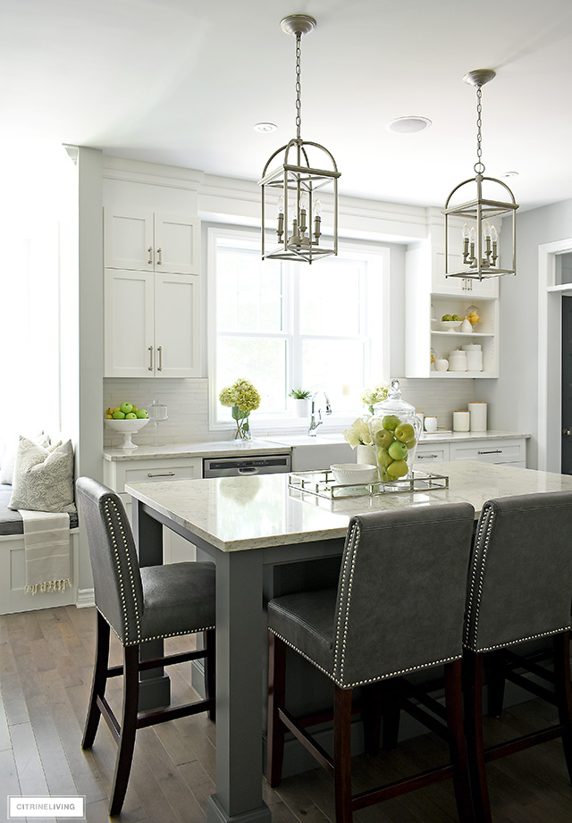 Classic white kitchen with grey island and silver pendant lights.