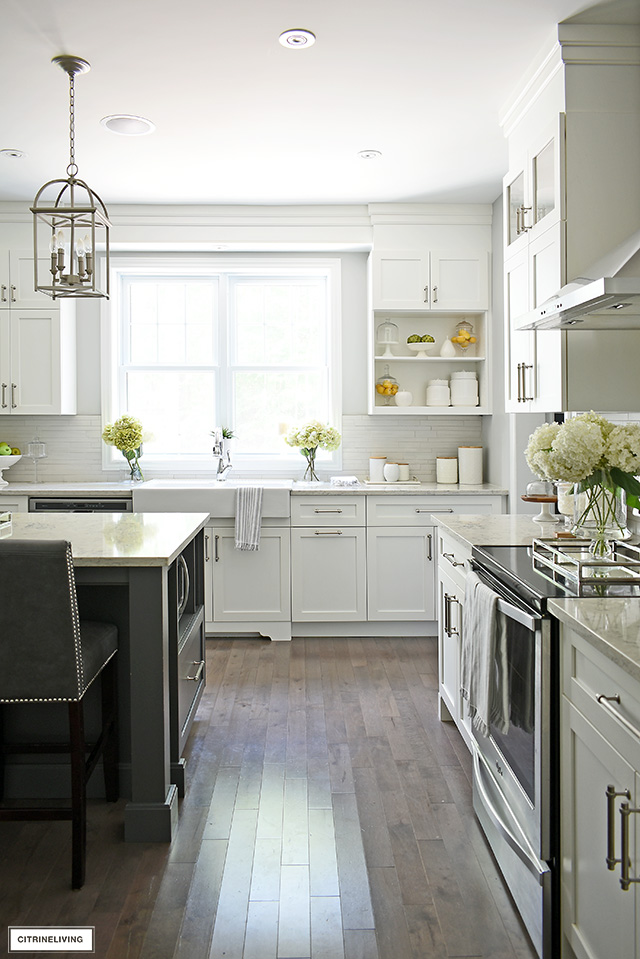 Bright and airy white kitchen with grey island, silver hardware and hardwood floors.