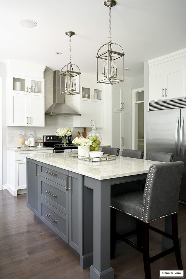 Gorgeous white kitchen with grey island, featuring Satin Nickel handles. Brushed silver pendant lights are elegant and sophisticated!