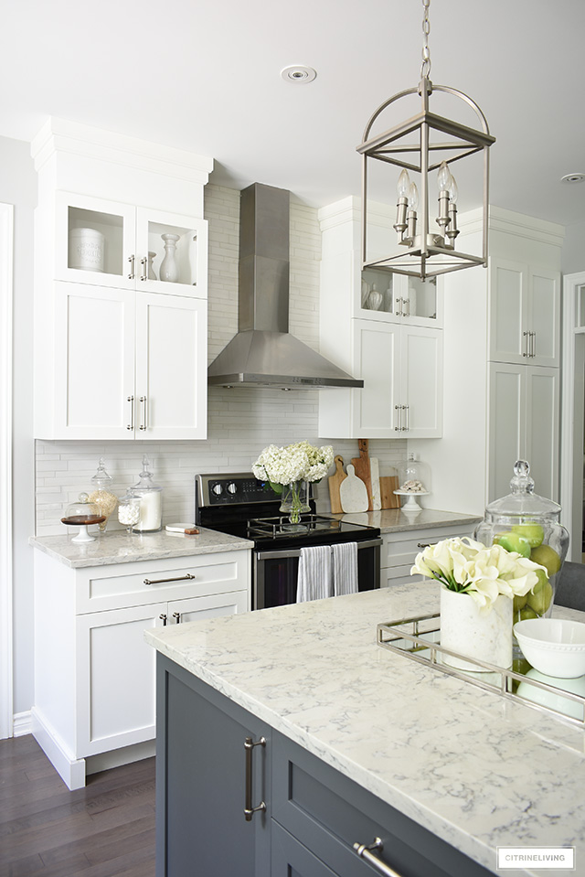 Gorgeous kitchen featuring white cabinets, grey island and brushed silver accents.
