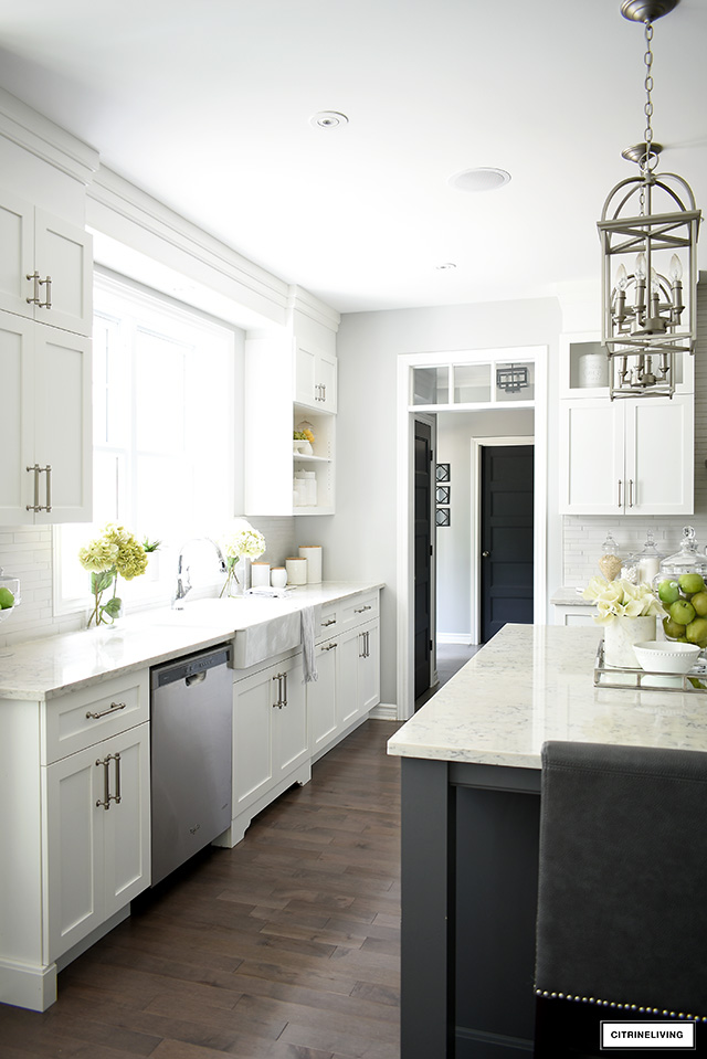 Beautiful classic white kitchen with brushed silver handles, white farm sink and hardwood floors.